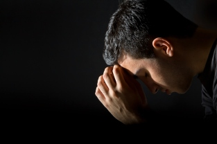 Man praying in dark room with ray of light on him